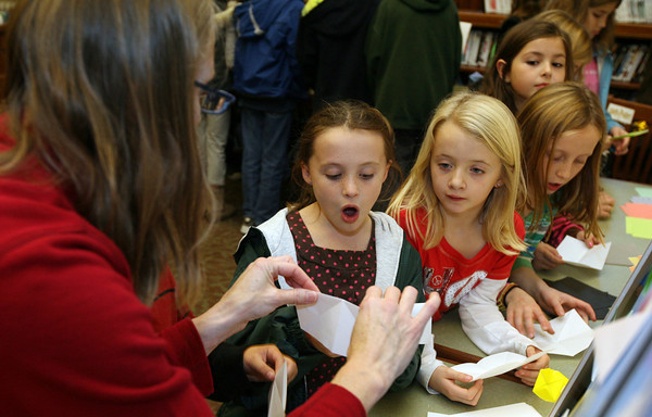 """Manchester: Laura Geggis shows Courtney Dellicker, Jennifer O'Neil, Caroline Dellicker and Eva Parker how to make a Golden Snitch using origami during """"Harry Potter Origami"""" at the Manchester Public Library on Tuesday. Other origami items from the popular series included a chocolate frog, Nimbus 2000 broomstick, serpent and howler. Photo by Kate Glass/Gloucester Daily Times"""