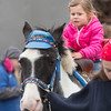 Desi Smith/Staff Photo.   Sienna Lehr 3, of Gloucester is lead around on a horse at Fallfest held Saturday at Cape Ann Marina. October 3,2015