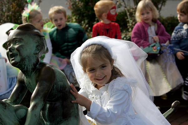 Rockport: Riley Campbell sits on the Richard Recchia staue The Baby on the Frog while posing wth her friends for a picture as the students from the Sandy Bay Preschool trick-or-treat at local buisnesses in downtown Rockport Friday. Mary Muckehoupt/Gloucester Daily Times