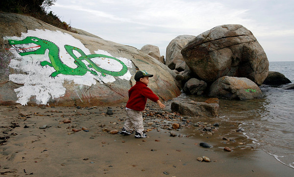 Gloucester: Evan Minatel, 2, tosses stones into the ocean at Cressy's Beach yesterday afternoon. The serpent was recently repainted on top of its old location. Photo by Kate Glass/Gloucester Daily Times Thursday, October 22, 2009