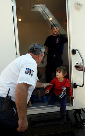 Manchester: Manchester Firefighter Tom Kehoe helps Gus Brown from the fire safety trailer as Firefighter Thomas Aldrich looks on yesterday morning. Students at Manchester Memorial School learned about fire safety, including how to call 911 and what to do when there's smoke in the room. Photo by Kate Glass/Gloucester Daily Times Tuesday, October 6, 2009