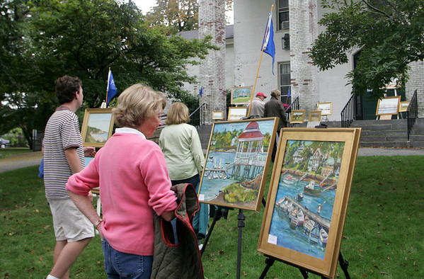 Manchester: Kate Ryan of Manchester checks out some painting by Mary Scannell during the art show put on by the Manchester Culteral Council in front of Manchester Town Hall Sunday morning. Several local artists had their work of Manchester landscapes on display and for sale. Mary Muckenhoupt/Gloucester Daily Times