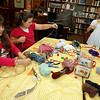 Manchester: Isabella Schmidt, Kailey Bachman, and Niamh Dalton weave webs at the Manchester Library yesterday afternoon. The webs were intended to be Halloween decorations, but Isabella said she was going to use hers to scare her little brother. Photo by Kate Glass/Gloucester Daily Times