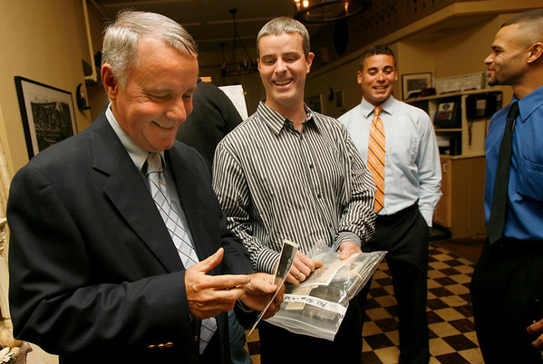 Rockport: Rockport DPW Senior Field Coordinator George Robertson, left, smiles as he looks at photos brought in by former colleague Mike McLaughlin, center, during Robertson's retirement party at Brackett's Oceanview Restaurant in Rockport last night. McLaughlin worked with Robertson for 11 of his 40 years with the town. Photo by Kate Glass/Gloucester Daily Times Thursday, October 8, 2009