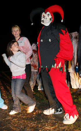 Gloucester: Kevyn Chandler, 7, takes a second glance at the joker that scared her and her mom, Caitlin Chandler, at the Camp Spindrift Haunted Woods. The haunting grounds will be open from 5 to 10 p.m. October 22-25, 29-30, and 5 to 9 p.m. on Halloween. The event is a fund-raiser for next year's Horribles parade. Photo by Kate Glass/Gloucester Daily Times Thursday, October 22, 2009