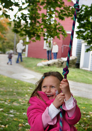 Essex: Maia Havrda, 7, swings on a rope tied to a tree at Cogswell's Grant during their Pumpkin Festival Saturday afternoon.  Maia was having a great time at the festival and had already gotten her face painted and taken a hayride out to a pumpkin patch. Mary Muckenhoupt/Gloucester Daily Times