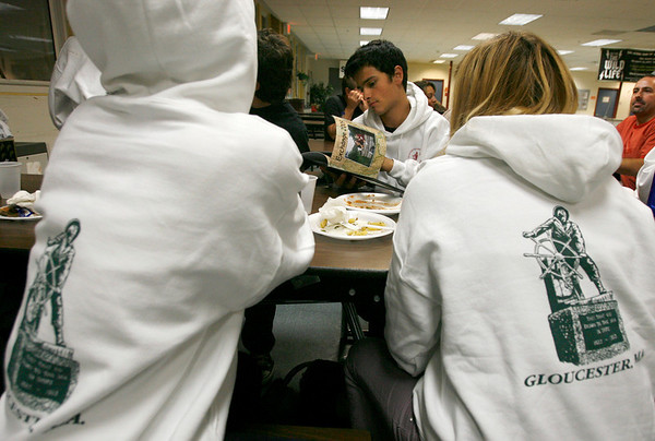 Gloucester: Francesco Passalacqua of Gloucester looks through a book of photos during a pot-luck dinner for Italian exchange students and their host families at the Gloucester High School cafeteria on Monday night . Eighteen students stayed with Gloucester families for two weeks and the dinner was the final group outing before they head to New York for a few days. The Passalacquas hosted Angelo Mazzette of Rome. Photo by Kate Glass/Gloucester Daily Times Monday, October 5, 2009