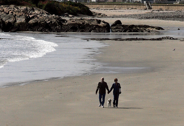 Rockport: Marc Olivere and his wife, Maureen Conboy, walk their dog, Nicholas, along an empty Cape Hedge Beach on Monday afternoon.