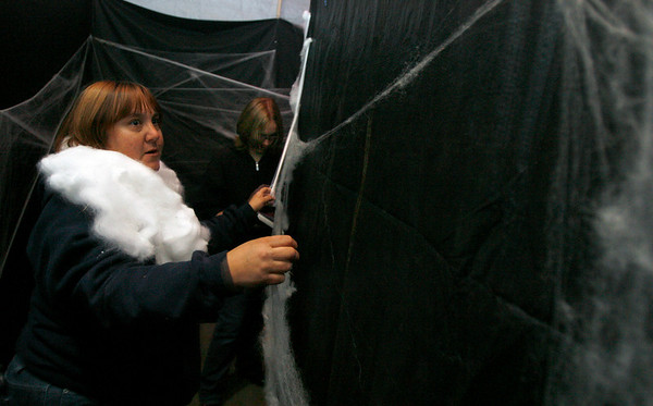 Gloucester: Heather Goolsby and her daughter, Cheryl Lynne Goolsby, hang spider webs in the maze at the Camp Spindrift Haunted Woods. The haunting grounds will be open from 5 to 10 p.m. October 22-25, 29-30, and 5 to 9 p.m. on Halloween. The event is a fund-raiser for next year's Horribles parade. Photo by Kate Glass/Gloucester Daily Times Thursday, October 22, 2009
