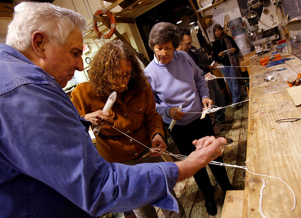 Gloucester: Tony Ashdon of Rockport teaches Alice Gardner of Beverly and Doris Cole of Gloucester how to make a net during a workshop at the Gloucester Maritime Heritage Center on Thursday night. Alice says she's watched fishermen mending nets at the Jodrey State Fish Pier and wanted to learn the technique. Photo by Kate Glass/Gloucester Daily Times Thursday, October 29, 2009