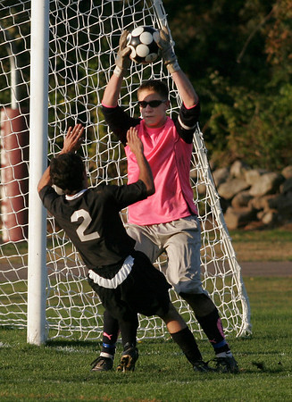 Rockport: Rockport keeper Keady Segel scoops up the ball as North Andover's Evan Boudreau slips on the turf yesterday. Photo by Kate Glass/Gloucester Daily Times Tuesday, October 20, 2009