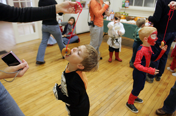 Gloucester: Colin Porter, 5, tries to eat a donut from a string during the Halloween party at Sandy Bay Preschool Friday morning. After the party kids went on a parade around town to trick-or-treat at local buisnesses. Mary Muckehoupt/Gloucester Daily Times