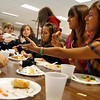 Gloucester: From right: Giulia Daga and Sara Santamaria, who are both visiting from Rome on an exchange program, take a plate of desserts during a pot-luck dinner at the Gloucester High School cafeteria on Monday night. Eighteen students stayed with Gloucester families for two weeks and the dinner was the final group outing before they head to New York for a few days. Also shown are (from left): Domenic and Grace Romeo of Gloucester, Giulia Bordicchini of Rome, and Lia Romeo of Gloucester. Photo by Kate Glass/Gloucester Daily Times Monday, October 5, 2009