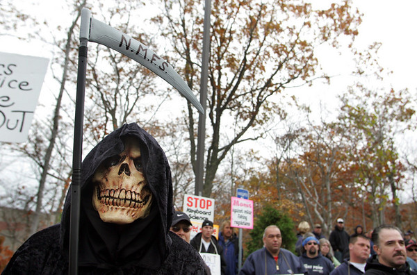 Gloucester: Dressed as the grim reaper, John DePoutiloff listens to fishing industry lawyer Stephen Ouellette speak at the protest against NOAA and NMFS regulations and enforcement tactics in front of the NOAA building at Blackburn Industrial Park Friday morning. Mary Muckenhoupt/Gloucester Daily Times