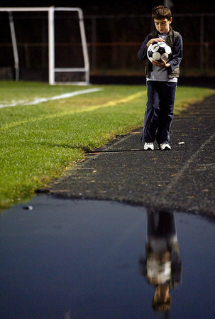 Gloucester: Kory Hurd, 9, dries off a soccer ball after it went into a puddle during the Gloucester boys soccer game at Newell Stadium on Tuesday evening. Hurd said his hands were cold, but he's loyal to the team and his brothers, Kevin and Kyle, who both play midfield. Photo by Kate Glass/Gloucester Daily Times Tuesday, October 13, 2009