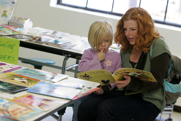 Rockport: Sally Woodson reads a book with her daughter Sarah, 4, at the annual Rockport book fair Wednesday afternoon.  Mary Muckenhoupt/Gloucester Daily Times