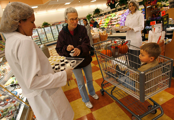 Gloucester: Cleone White of Gloucester selects a cake sample for her grandson, Brett Cunningham, 4, from Margaret Miranda while shopping at Market Basket yesterday. White says they only came to look, but ended up doing a little shopping. Photo by Kate Glass/Gloucester Daily Times Wednesday, October 7, 2009