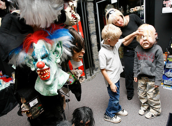 Gloucester: Chrissy Walsh and her son, KC, 7, help Ryan Bergin, 6, put on a mask at the Joke Shop yesterday afternoon. Ryan says he already has his vampire costume for Halloween, but thinks his older brother should check out the store. Photo by Kate Glass/Gloucester Daily Times Tuesday, October 20, 2009