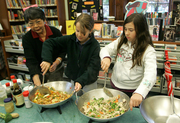 Manchester: Norma Chang helps Lucy St. Clair and Sara Stanton, right, stir-fry chicken and vegetables during Chang's Chinese cooking demonstration at the Manchester Public Library.  Chang showed children ages ten and older how to make healthy Chinese dishes that are simple and easy to make. Mary Muckenhoupt/Gloucester Daily Times