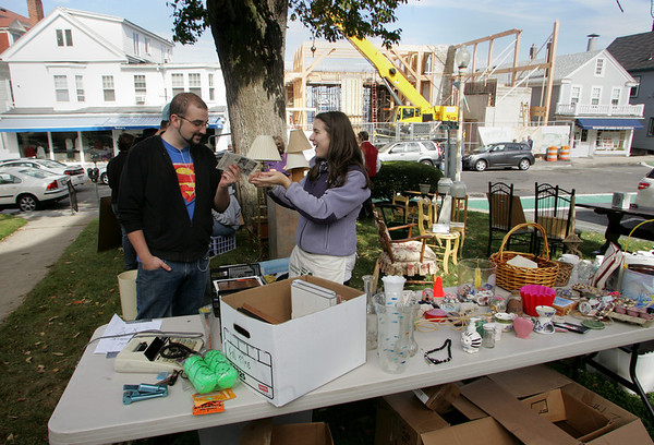 Rockport: Cassie Balzarini, 17, shows Kyle Picardo some scracth and sniff iron-on decals she found while organizing one of the tables of the yard sale in front of the First Congregational Church Saturday. The yard sale was held to raise money for the church's youth group's mission trip to Buffalo, New York to repair houses this June. Mary Muckenhoupt/Gloucester Daily Times