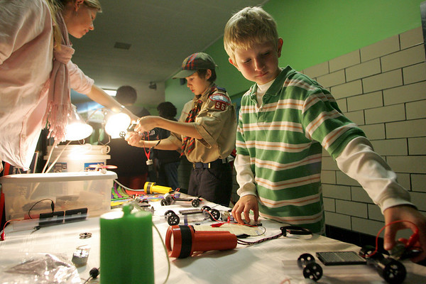 """Gloucester: Cole Ventimiglia, 9, right, and Benjamin Hunter, 11, play at the solar cars exhibit run by Jennifer Kuhns, left, during Go Green Night as part of Nationa Grid's """"Power to Save"""" program at West Parish Elementary School Friday night. Mary Muckenhoupt/Gloucester Daily Times"""