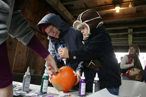 Essex: Gabriel Fitanides, 3, works on decorating a pumpkin by adding blue hair with the help of his grandmother, Mary Maffucci-Fitanides at the Cogswell's Grant Pumpkin Festival Saturday afternoon. The festival included such activities as hayrides, face painting, and pumpkin carving. Mary Muckenhoupt/Gloucester Daily Times