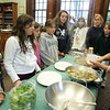 Manchester: Norma Chang shows how to thicken broth with corn starch and water while making stir-fry at the Manchester Public Libray Saturday morning. Chang came to the library to give a Chinese cooking demonstration for anyone over the age of ten and taught how to make easy, healthy meals. Mary Muckenhoupt/Gloucester Daily Times.