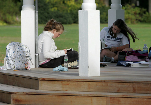 Manchester: Abbie Buck, left, reads a book while Tatum Hosman works on her homework as the girls wait for field hcokey practice to start Thursday afternoon at Masconomo Park. Mary Muckenhoupt/Gloucester Daily Times