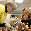 Gloucester: Makayla Mateo, 5, of Gloucester shows Lucille LePage's puppet Rosebud a little book just big enough for a little kid or a little puppet to read at the Sawyer Free Library.  Storyteller Lucille LePage came to the library to tell spooky stories for Halloween Saturday morning. Mary Muckenhoupt/Gloucester Daily Times