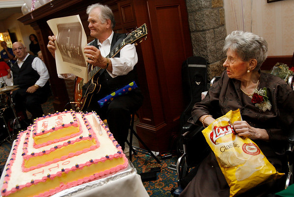 Gloucester: Edna New eats a few potato chips as she is presented with a poster of her favorite band, Manuel's Black & White Orchestra, during her 110th birthday party at Seacoast Nursing and Rehab Center yesterday. New eats a bag of potato chips every day and credits them with allowing her to stay healthy so long. Photo by Kate Glass/Gloucester Daily Times Tuesday, October 13, 2009