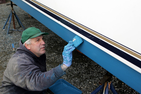 Essex: Ivan Muise of Essex works on painting a friend's boat at Perkins Marine Thursday afternoon. Mary Muckenhoupt/Gloucester Daily Times