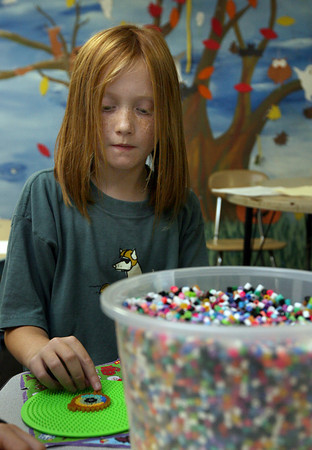 Rockport: Perry Wilson creates a design using plastic beads that fuse together when heated with an iron during the YMCA's after school program at Rockport Elementary School. Photo by Kate Glass/Gloucester Daily Times