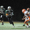 Manchester:  Manchester's Alex Carr hands the ball off to #28 against Ipswich Tigers as the rain comes down. Desi Smith/Gloucester Daily Times. October 15,2010.