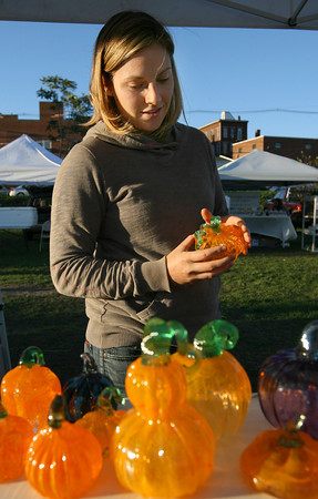 Gloucester: Jenny Doane of Gloucester looks through glass pumpkins on Aron Leaman's table at the Cape Ann Farmers Market yesterday afternoon. Yesterday was the last day of the market. Photo by Kate Glass/Gloucester Daily Times