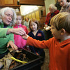 Manchester: Barbara Emerson hands Cole Cote, 4, of Manchester a worm from her worm composter at the Manchester Public Library Saturday morning.  Emerson lead an informative discussion on worm composting and how easy it can be. Mary Muckenhoupt/Gloucester Daily Times