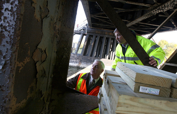 Gloucester: Frank DePaola, the MBTA's Assistant General Manager of Design and Construction, points out some of the rusting steel beneath the Railroad Bridge to State Senator Bruce Tarr during a tour of the bridge yesterday. The MBTA is looking to replace the drawbridge, which is over 100 years old. Photo by Kate Glass/Gloucester Daily Times