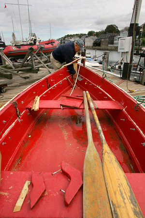 Rockport: Ben Loiacono works of fixing the bow of one of the red skiffs that belongs to the Sandy Bat Yacht Club Thursday afternoon.  The boat got loose and was found on the rocks of Straightsmouth Island and was returned by the Thatcher Island launch.  Mary Muckenhoupt/Gloucester Daily Times