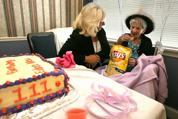 Gloucester: Darlene Richards chats with Edna New as she eats Lays potato chips during the celebration of her 111th birthday at Seacoast Nursing & Rehabilitation Center yesterday afternoon. Edna eats a bag of potato chips a day and credits them for her longevity. Photo by Kate Glass/Gloucester Daily Times