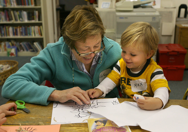 Essex: Katherine Bamberger helps her grandson, Max Fritsch, decorate a scarecrow at the TOHP Burnham Library during story hour yesterday morning. Photo by Kate Glass/Gloucester Daily Times