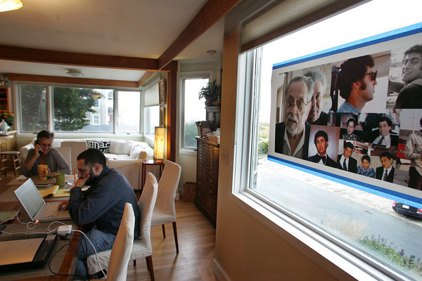 Gloucester:  Kate Seidman, the wife of Mitch Cohen, and Cohen's son Aaron Cohen, sit at their kitchen table with a photo collage of Mitch in the window of their Gloucester home Thursday afternoon. Mitch Cohen past away ??????????????????  Mary Muckenhoupt/Gloucester Daily Times