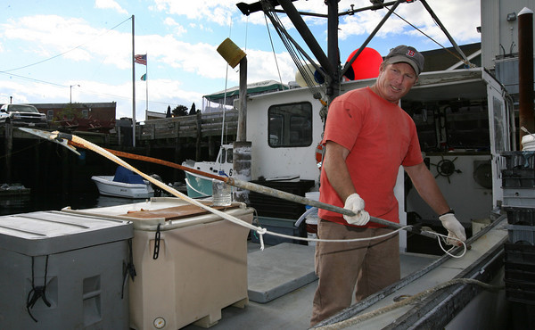 Gloucester: Mark Carroll greases harpoons as he prepares his boat, Harvest Moon, to go tuna fishing. Photo by Kate Glass/Gloucester Daily Times