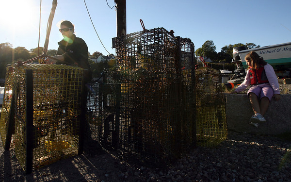 Rockport: Marlena Kolterjahn unloads lobster traps from their family boat at the Old Granite Pier as her daughter, Madison Kolterjahn, sits nearby. They were happy they had been able to continue lobstering until this late in October, but ready to call it a season. Photo by Kate Glass/Gloucester Daily Times