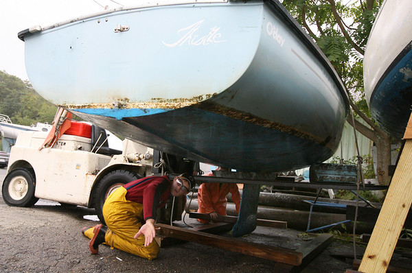 Gloucester: Ryan Sears and Scott Anderson, rear, build a crate to store one of the sailboats used by Sail GHS at Beacon Marine yesterday afternoon. The program's boats are being stored there for the winter. Photo by Kate Glass/Gloucester Daily Times