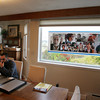 Gloucester: Mitch Cohen's son Aaron Cohen, sit at the kitchen table with a photo collage of his father in the window of Cohen's Gloucester home Thursday afternoon. Mitch Cohen past away ??????????????????  Mary Muckenhoupt/Gloucester Daily Times