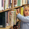 Manchester: Addison Lai, 2, of Manchester looks through the books in the children's room at the Manchester Public Library Saturday afternoon. Addison was more interested in pulling the book out onto the floor than actually looking through them. Mary Muckenhoupt/Gloucester Daily Times