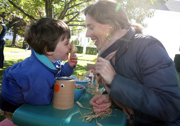 Rockport: Henry Chadbourne tells a secret to his mom, Margaret Chadbourne, while making a scarecrow monster at the Sandy Bay Preschool booth during the Rockport Harvest Festival on Saturday. Photo by Kate Glass/Gloucester Daily Times