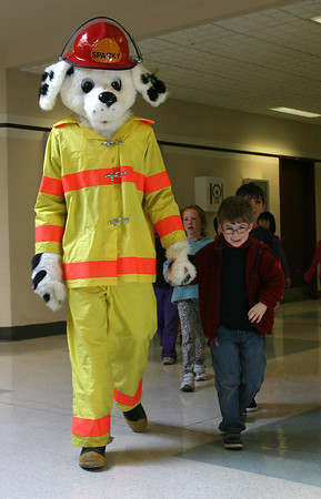 Rockport: Damien Sorrenti smies as he holds Sparky's hand while leading his first grade class outside to look at Rockport's fire trucks during a demonstration at the Elementary School yesterday morning. Photo by Kate Glass/Gloucester Daily Times