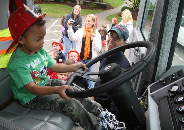 "Essex: Cole Thomas takes a turn behind the wheel of an Essex Fire Truck outside Lil' Sprouts of Essex as Manchester Firefighter Dennis Pyburn looks on yesterday morning. The firefighters did a presentation as part of Fire Prevention Week to teach children not to be afraid of firefighters, get out of buildings safely, and stop drop and roll. The Manchester Fire Department will be visiting Memorial School today as well as having an open house at the Fire Station at 6 p.m. The Essex Fire Department will be hosting a ""Touch a Truck"" event on Thursday from 4-7 in conjunction with the Friends of the TOHP Burnham Library. Rockport and Gloucester had no scheduled events. Photo by Kate Glass/Gloucester Daily Times"