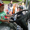 """Essex: Cole Thomas takes a turn behind the wheel of an Essex Fire Truck outside Lil' Sprouts of Essex as Manchester Firefighter Dennis Pyburn looks on yesterday morning. The firefighters did a presentation as part of Fire Prevention Week to teach children not to be afraid of firefighters, get out of buildings safely, and stop drop and roll. The Manchester Fire Department will be visiting Memorial School today as well as having an open house at the Fire Station at 6 p.m. The Essex Fire Department will be hosting a """"Touch a Truck"""" event on Thursday from 4-7 in conjunction with the Friends of the TOHP Burnham Library. Rockport and Gloucester had no scheduled events. Photo by Kate Glass/Gloucester Daily Times"""