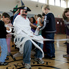 Rockport: Students in Darlene Trumbour's multi-age 1st and 2nd grade class wrap principal Sean McGuire in toilet paper during an assembly Friday morning.  Trumbour's class won for most participation in the school's wrapping paper drive so they were the one's who got to wrap the principal head to toe. Pictured, from left, Matthew Tucker, Linden Adamson and Kayla Colbert, and Gus Johnson. Mary Muckenhoupt/Gloucester Daily Times